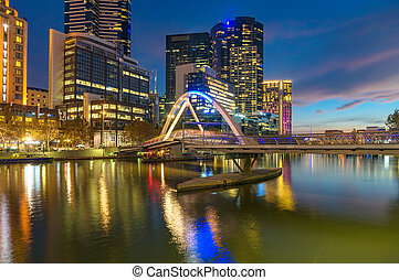 Beautiful cityscape at night with bridge across river -...