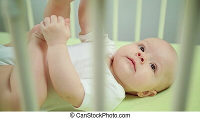 Baby Lying in a Crib and Playing