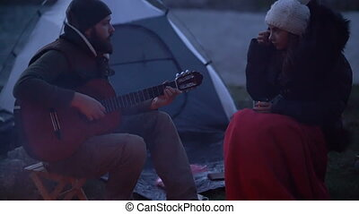 Couple of travelers at dusk near a campfire, romantic...