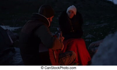 Couple of travelers at dusk near a campfire