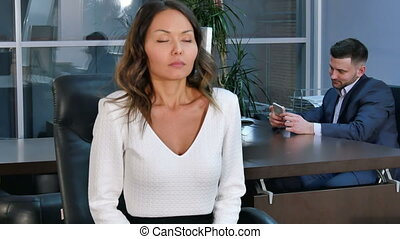 Young healty office woman doing fitness exercise at workplace, while sitting in office chair