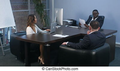 African businessman signing employment contract in office...