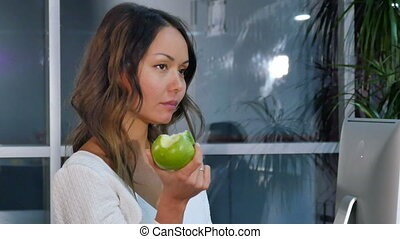 Pretty businesswoman eating green apple in the office....
