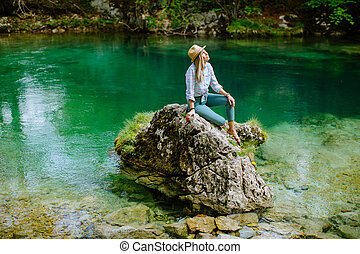 woman relax at mountain lake view. Auhentic Blonde woman...
