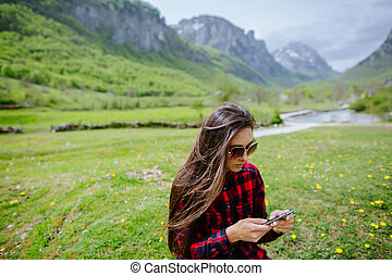woman with smartphone backpacking in mountains. Brunette...