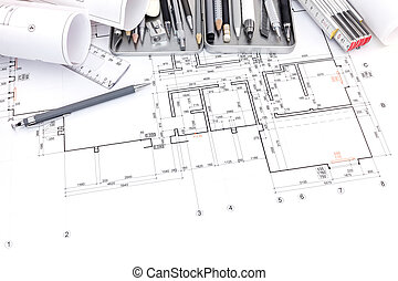 set of various drawing tools on paper with graphical plan and blueprint rolls