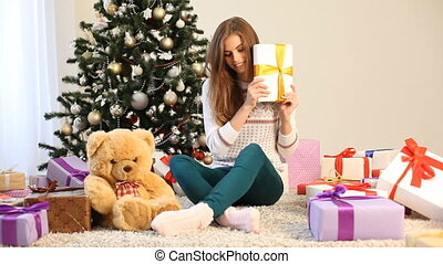 the girl sitting by the Christmas tree and gifts opens - the...