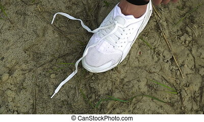 girl ties the laces on white sneakers - close up of girl...