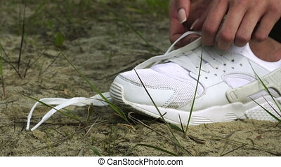 a woman ties a white shoelace - close up of woman ties a...
