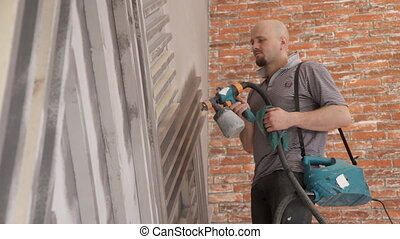 Young European makes repairs in apartment washing...