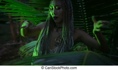 Beauty in the jungle - Beautiful woman with braids dancing...