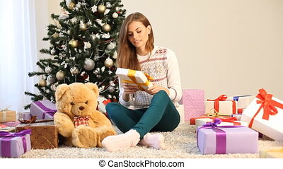 the girl sitting by the Christmas tree and Christmas gifts...