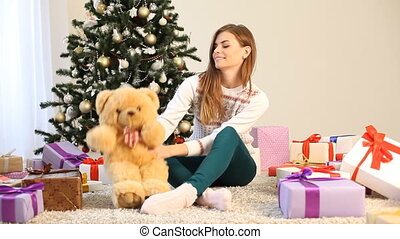 pretty girl sits with a teddy bear and presents