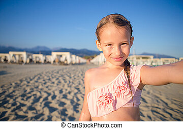 Happy little girl taking selfie at tropical beach on exotic...