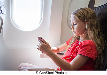 Adorable little girl traveling by an airplane. Kid listening...
