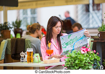 Beautiful woman sitting in a cafe outdoor with map. Happy...