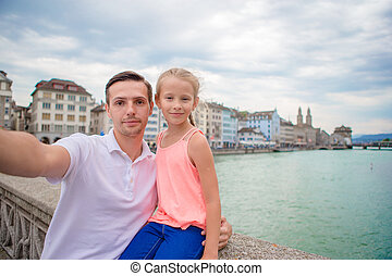 Young dad and daughter taking selfie background famous...