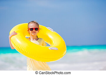 Happy kid with inflatable rubber circle having fun on the...