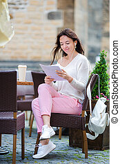 Beautiful woman sitting in a cafe outdoor drinking coffee....