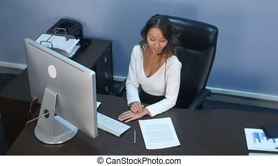 Attractive young asian woman working in a call center. Top...