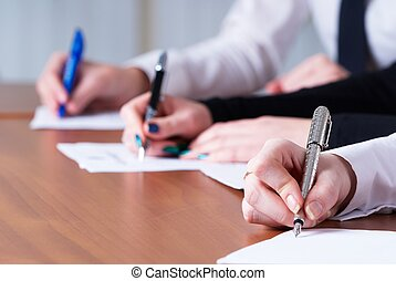 Writing girl - Young business women writing document in...