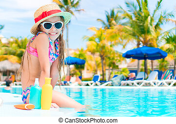 Little girl with bottle of sun cream sitting on the edge of...