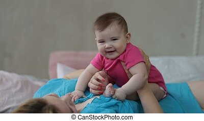 Portrait of excited baby infant laughing in bed - Closeup of...