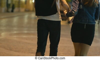 Young couple running through the night city