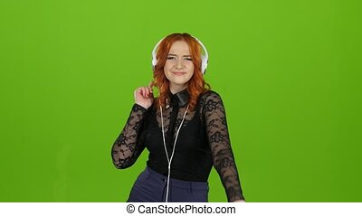 Redhaired girl begins to dance, she is in a good mood. Green...