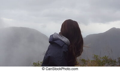 Woman traveler sitting on the edge of beautiful canyon and...