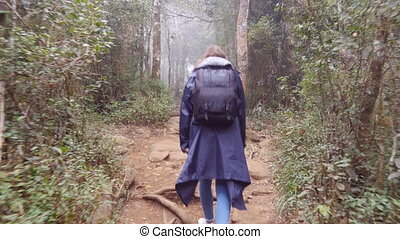 Young girl in raincoat with backpack going on exotic wood...
