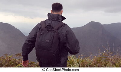 Young male hiker in raincoat with backpack reaching up top of mountain and raised hands. Man tourist standing on the edge of beautiful canyon, victoriously outstretching arms up. Rear back view