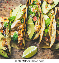 Tacos with chicken, avocado, fresh salsa and limes, square...
