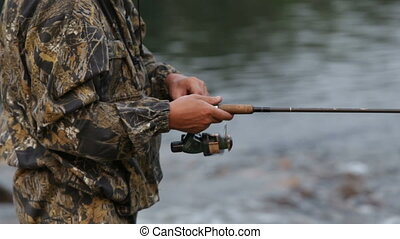 A man in camouflage clothes is fishing for spinning