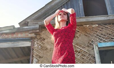 Beautiful lifestyle girl in a red dress. Sexy girl in a dress is standing next to the old house of the ruins