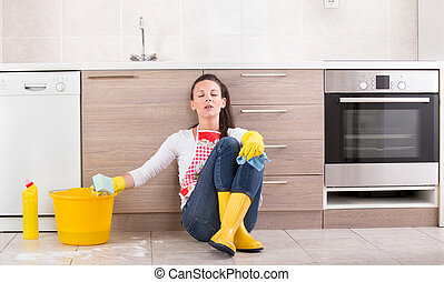 Tired housekeeper sitting on kitchen floor - Tired young...