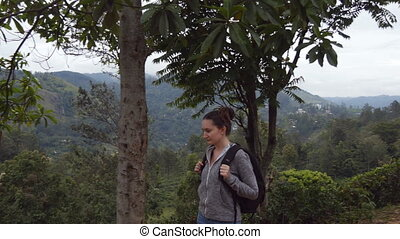 Female hiker going along tropical mount road. Young woman tourist with backpack walking at trail in mountains with beautiful nature landscape at background. Healthy active lifestyle. Travel concept