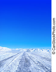 winter road - Snow covered road in winter with mountains in...