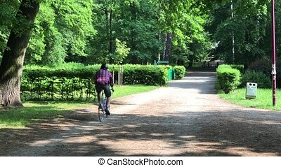Man riding in the park - Young man riding his bike in the...
