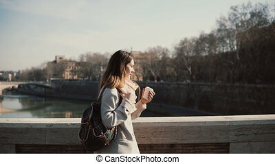 Young beautiful woman walking in the sunny morning on the...