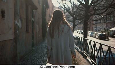 Back view of young woman with long hair walking in the...