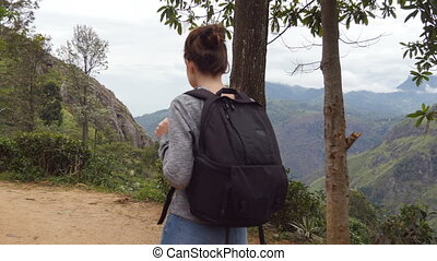 Young woman tourist with backpack walking at trail in mountains with beautiful nature landscape at background. Female hiker going along tropical mount road. Healthy active lifestyle. Summer vacation