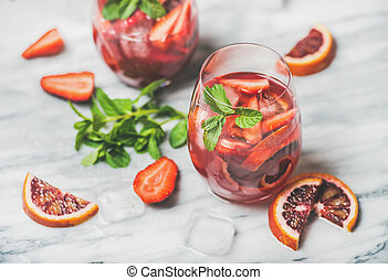 Fruit refreshing Sangria cocktails with ice and mint, marble background