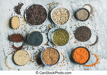 Variety of raw grains, beans, cereals over marble background