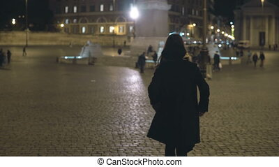 Young woman walking in the evening city alone. Attractive female waiting somebody in the city centre, at the square.