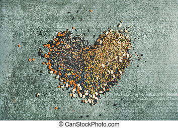 Various raw grains, beans and cereals in shape of heart