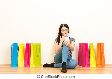 woman sitting on a white wall with wooden floor - surprised...