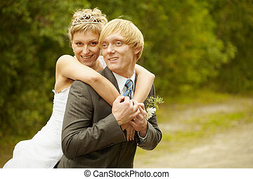 Happy young bride and groom hugging outdoors