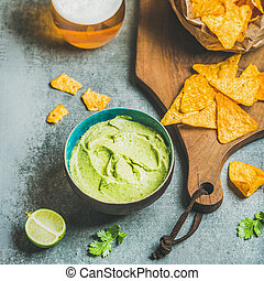 Mexican corn chips, fresh guacamole sauce and beer, square...