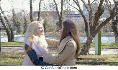 Two beautiful blonde and brunette girls meet for a walk in...